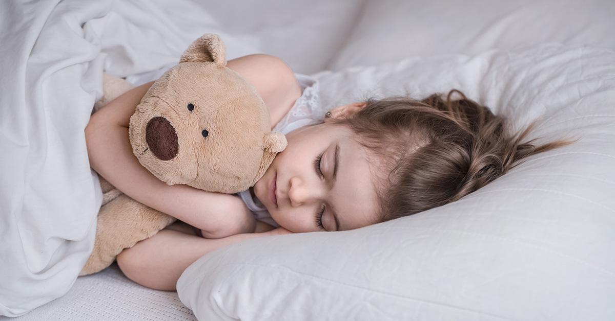 Bambina che dorme con il suo orsacchiotto