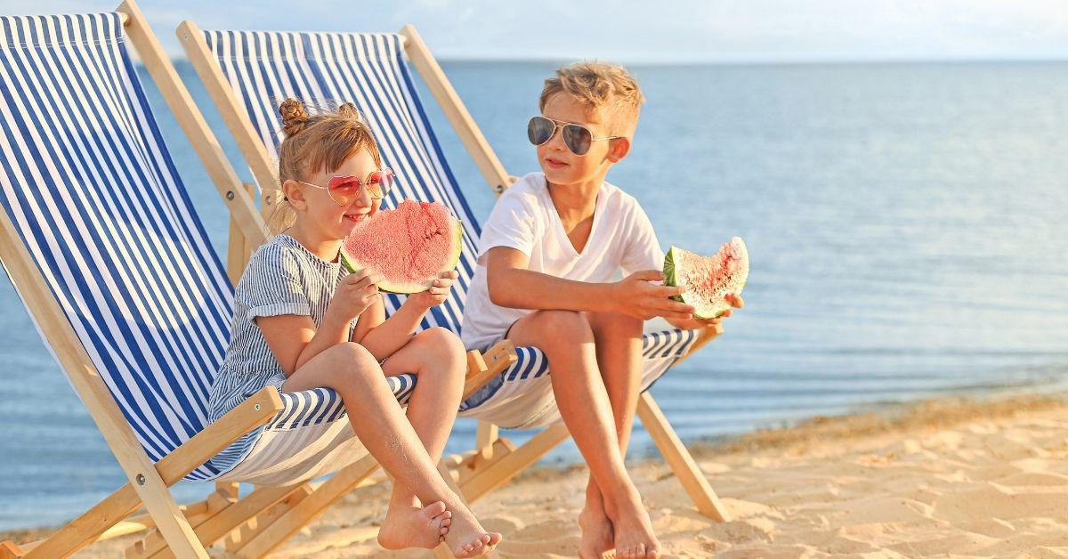 Bambini che mangiano in spiaggia e aspettano per fare il bagno